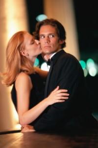 Donna che bacia l'uomo e uomo che guarda altrove