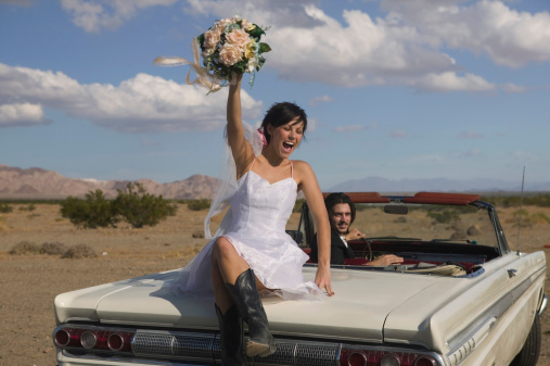 Excited bride with groom driving convertible