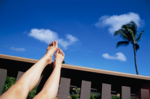 Legs up on a balcony with view of a blue sky and a palm tree